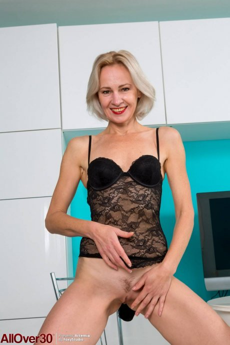 Blonde MILF Artemia playing with her shaved pussy in the kitchen at AllOver30