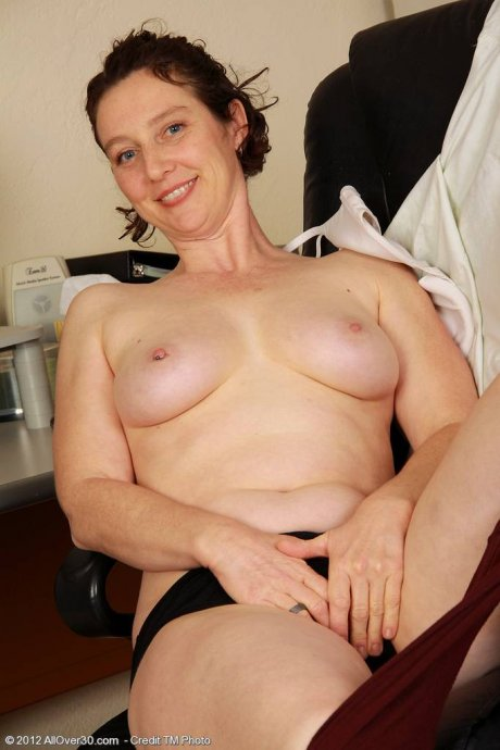 Mature mom Artemesia shows off her pussy in the office at AllOver30