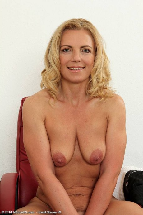Blonde mature Britney spreading her legs on the desk at AllOver30