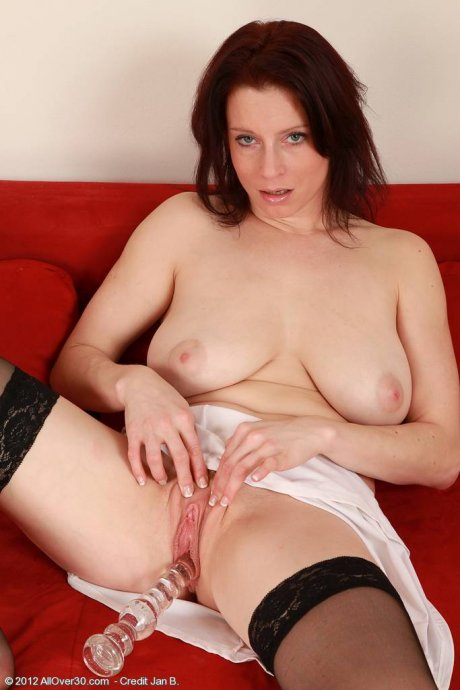 Mature housewife Carol firmly plants a large glass dildo inside at AllOver30
