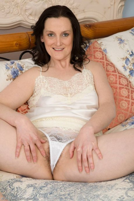 Hairy mature lady playing with herself on the bed at AllOver30