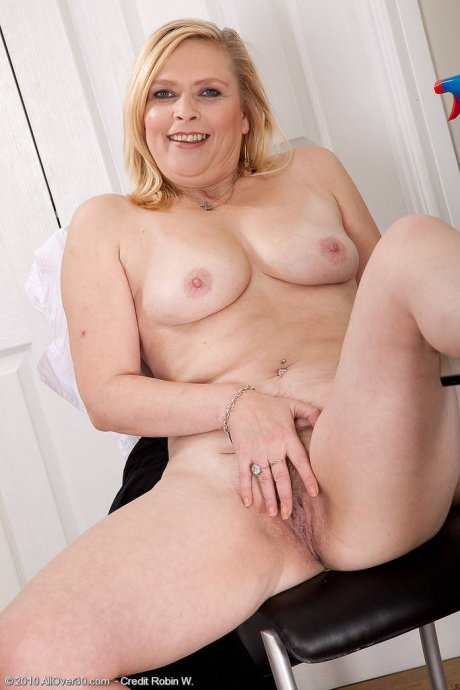 Blonde mature model Tamara strips after dusting the table at AllOver30