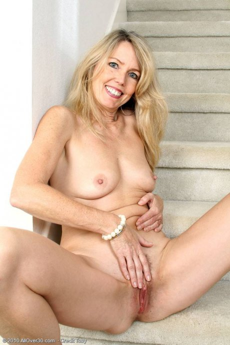 Blonde MILF Ginger B spreads her ass wide for you on the stairs at AllOver30