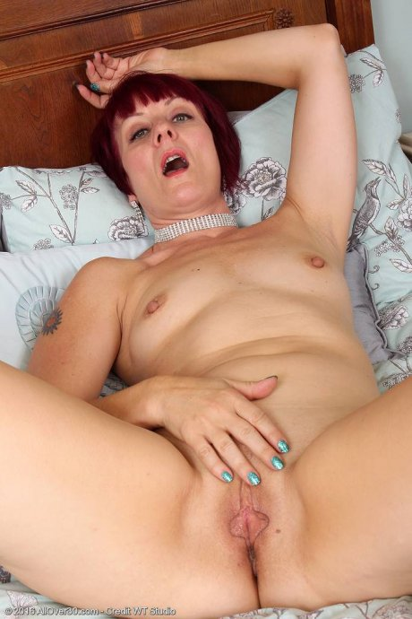 Redhead mature Penny Brooks playing with her shaved pussy at AllOver30
