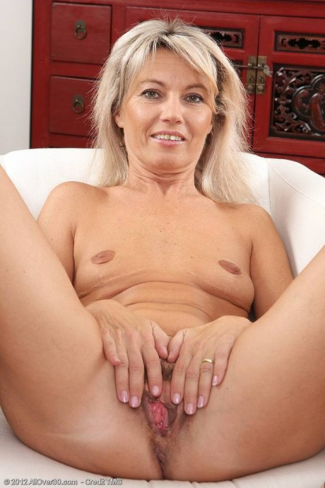 Blonde mature housewife stuffs a finger into her mature and trimmed pussy at AllOver30