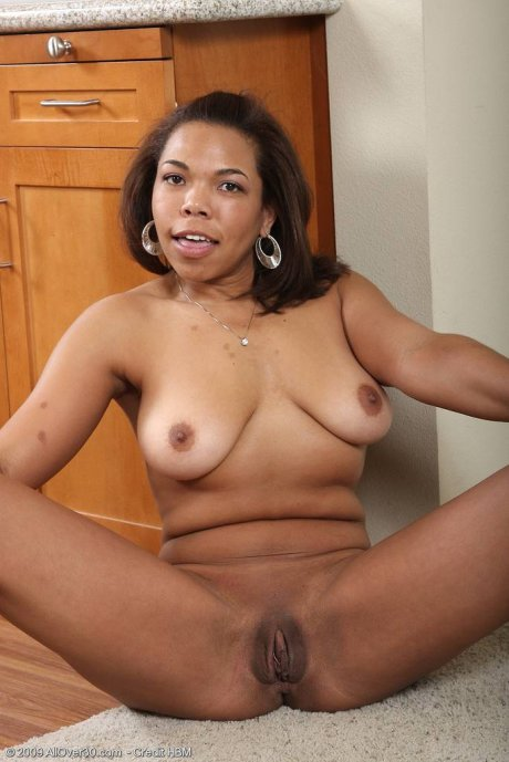 Ebony MILF Rena quickly peels her tight clothes in the kitchen at AllOver30