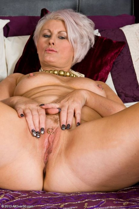 Blonde housewife Sally T exporing her mature shave pussy in bed at AllOver30