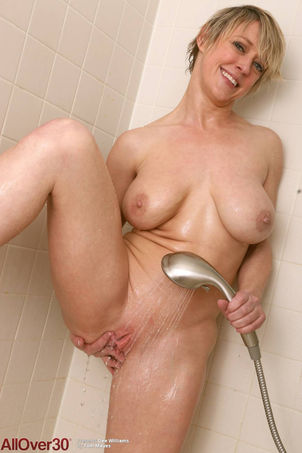 Blonde mature Dee Williams playing with her pink pussy on the shower at AllOver30