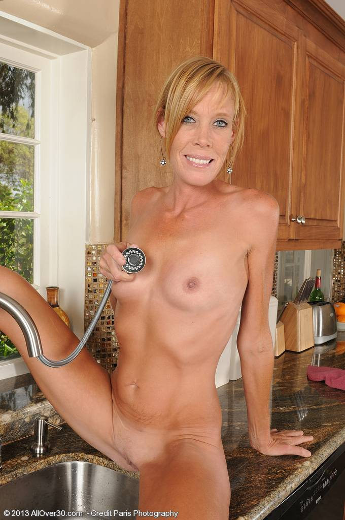 Blonde housewife Stacey Y sprays down her pussy at the kitchen sink at AllOver30