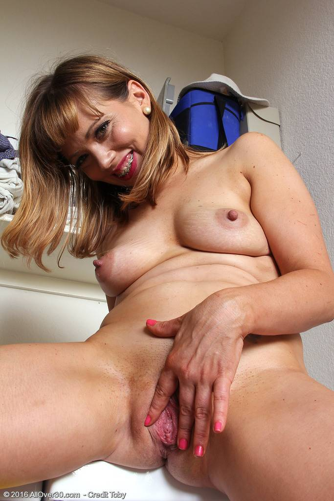 Sexy Christy James shows her braces as she does laundry at AllOver30